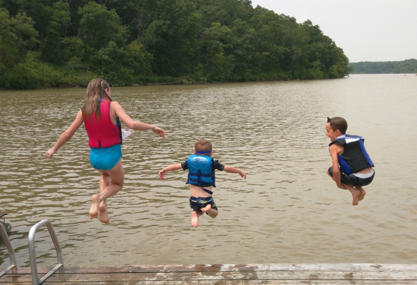 kids jumping into a lake