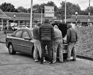 picture of people checking under the hood of a car